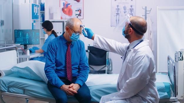 Lekarz mierzący temperaturę chorego pacjenta w masce ochronnej w prywatnym szpitalu lub klinice podczas pandemii covid-19. koncepcja sprawdzania koronawirusa sprzętu medycznego działającego w celu zapobiegania