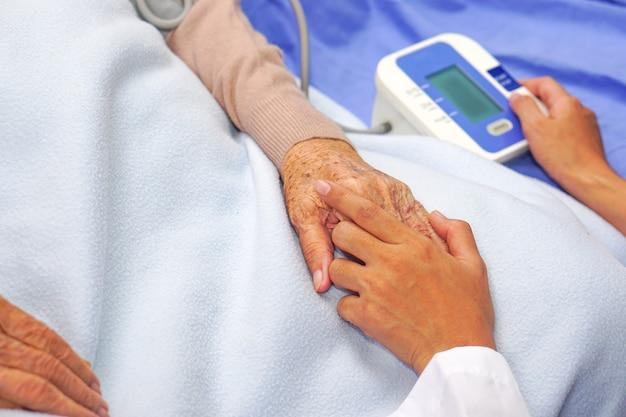 Lekarz mierzy ciśnienie azjatycki starszy