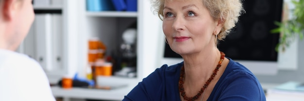 Lekarz mierzy ciśnienie krwi starszej kobiety w gabinecie lekarskim