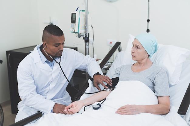 Lekarz mierzy presję na kobietę.