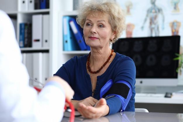 Lekarz mierzy presję starszej kobiety.