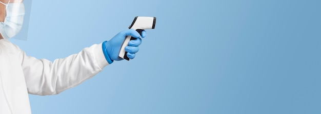 Lekarz mierzy temperaturę białym termometrem na podczerwień na niebieskim kolorze
