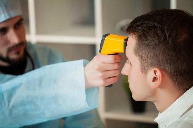 Lekarz mierzy temperaturę pacjenta za pomocą termometru laserowego.