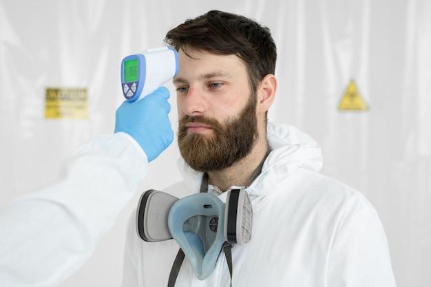 Lekarz mierzy temperaturę termometrem na podczerwień do swojego kolegi chorób zakaźnych. portret mężczyzny lekarz naukowiec w fartuchu. pojęcie koronawirusa