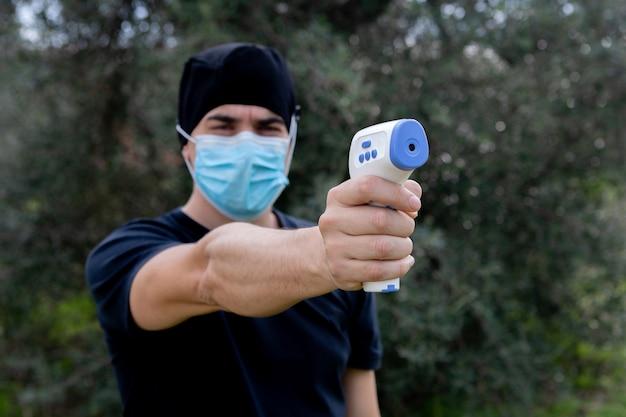 Lekarz mierzy temperaturę z termometrem na podczerwień