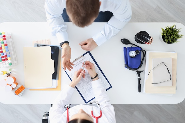 Lekarz mówi do pacjenta w biurze widok z góry. zbiór koncepcji historii medycznej
