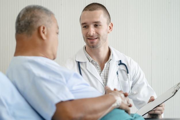Lekarz mówi do starszych pacjentów na łóżku w szpitalu.