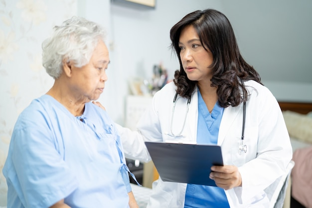Lekarz mówi o diagnozie i notatce w schowku z azjatycką starszą lub starszą kobietą, leżąc na łóżku na oddziale szpitala pielęgniarskiego, zdrowa, silna koncepcja medyczna.