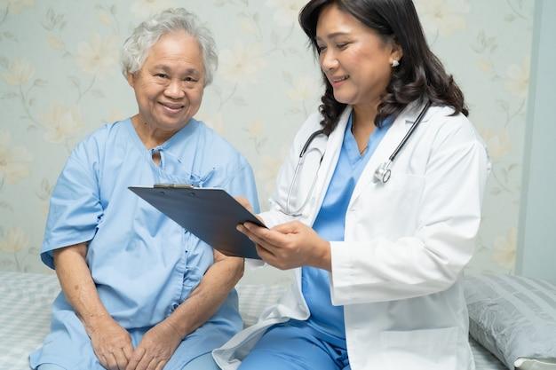 Lekarz mówi o diagnozie z pacjentem azjatyckim starszy kobieta w szpitalu