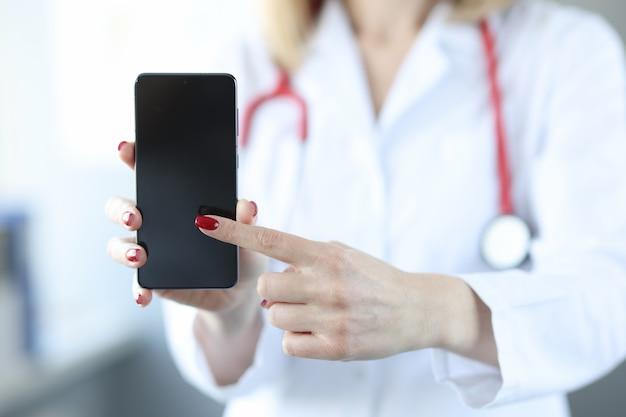 Lekarz naciskając palcem na ekranie zbliżenie telefonu komórkowego. koncepcja połączenia lekarza