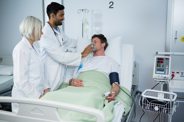 Lekarz nakłada maskę tlenową na twarz pacjenta