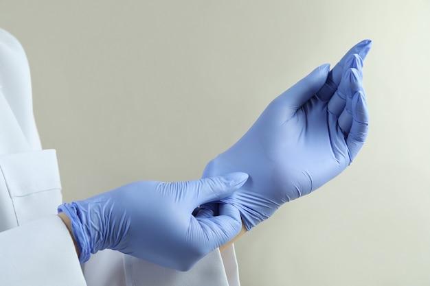 Lekarz nakłada rękawiczki medyczne na jasnoszarym na białym tle