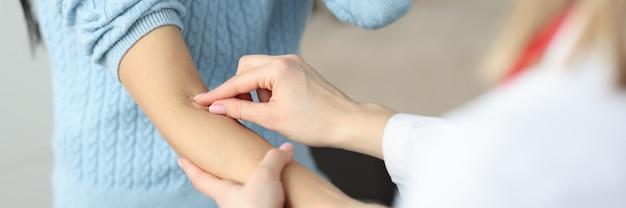 Lekarz nakładający łatkę na przedramię pacjenta w klinice zbliżenie zasady pobierania krwi z żyły
