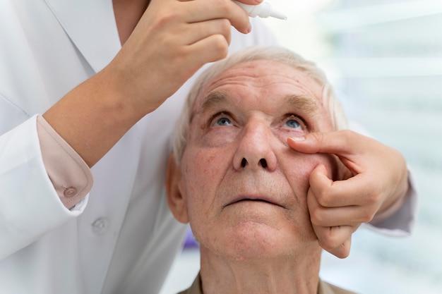 Lekarz nalewający krople do oczu dla pacjenta