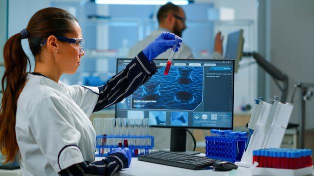 Lekarz naukowiec patrząc na próbkę krwi i pisania na komputerze, podczas gdy współpracownik otwiera drzwi za pomocą komputera cyfrowego z skanowaniem dotykowym. kobieta badająca ewolucję wirusa za pomocą zaawansowanych technologii i narzędzi chemicznych
