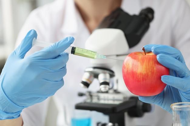 Lekarz naukowiec robi zastrzyk do jabłka w koncepcji laboratoryjnego leczenia antybiotykami