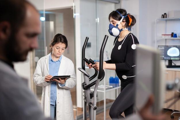 Lekarz naukowiec trzymając tablet pc i kontrolując dane ekg wyświetlane na monitorach laboratoryjnych. badacz laboratoryjny mierzący wytrzymałość sportowca, tętno za pomocą elektrod i maski.