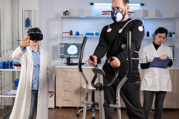 Lekarz naukowiec w sportowym laboratorium naukowym noszący gogle wirtualnej rzeczywistości podczas biegania sportowca, z elektrodami przymocowanymi do ciała, monitorujący wytrzymałość fizyczną, podczas gdy skanowanie ekg przebiega na ekranie komputera