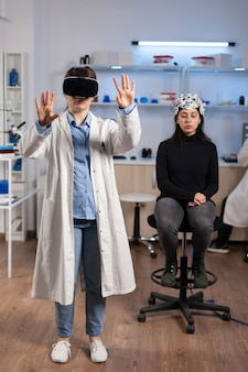 Lekarz neurobiologii gestykuluje w goglach vr podczas badań nad mózgiem, pacjent ze skanerem neurologicznym w laboratorium. lekarz szuka diagnozy, eksperymentu, np. laboratorium medycznego.