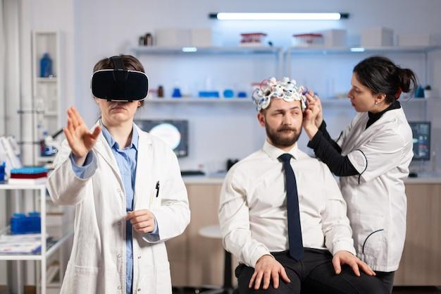 Lekarz neurolog wskazujący noszenie zestawu słuchawkowego rzeczywistości wirtualnej i asystenta dostosowującego czujnik pacjenta, który odczytuje aktywność mózgu, układ nerwowy. neurobiolog analizujący diagnozę.