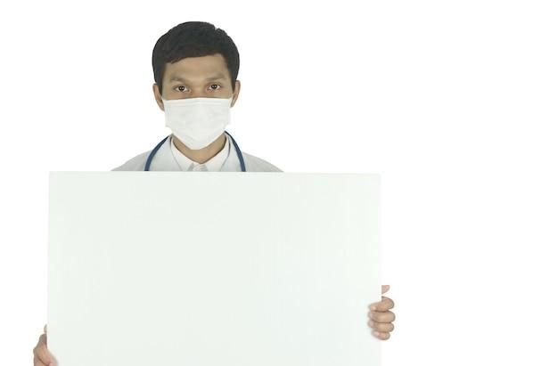 Lekarz nosi maskę medyczną ze stetoskopem, trzymając biały billboard i miejsce na kopię
