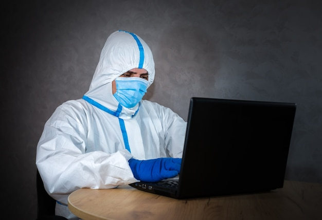 Lekarz nosi medyczny kombinezon ochronny, maskę medyczną i rękawiczki, pracuje na laptopie. ochrona przed epidemią wirusa. koronawirus (covid-19). pojęcie opieki zdrowotnej. praca zdalna w pandemii.