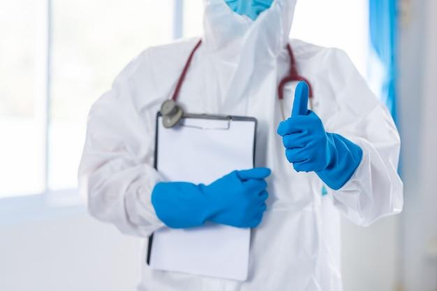 Lekarz nosi ppe kciuki w górę / lubię to i ściska koronawirusa