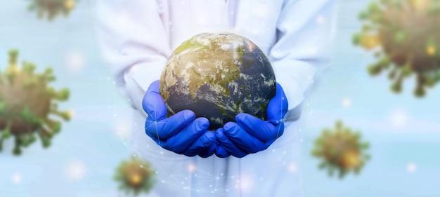 Lekarz nosi rękawiczki, które chronią ziemię przed sztandarem wirusa