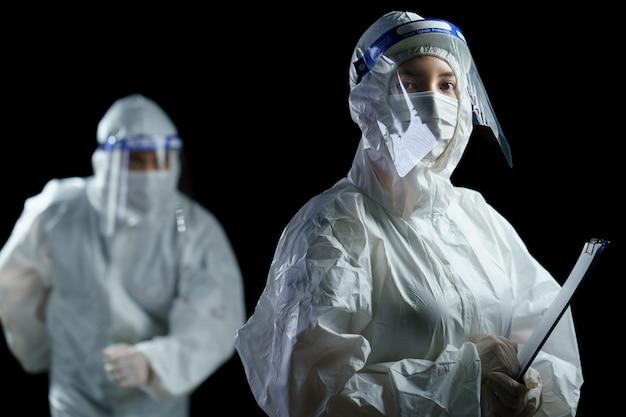 Lekarz nosi środki ochrony indywidualnej i osłonę twarzy biorąc raport