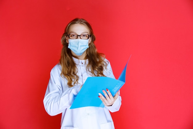 Lekarz noszący maskę otwiera i sprawdza historię pacjenta.