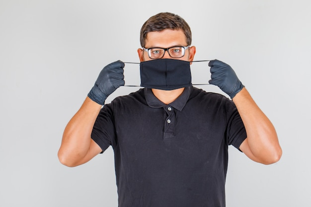 Lekarz noszący maskę w czarnej koszulce polo i patrząc poważnie