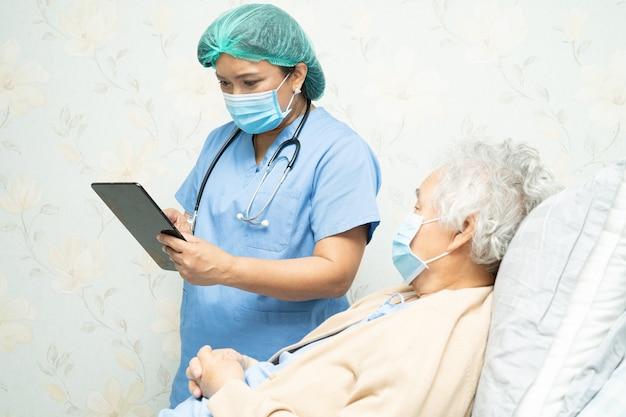 Lekarz noszący osłonę twarzy i środki ochrony indywidualnej pasuje do nowego, normalnego tabletu cyfrowego do wyszukiwania danych na temat infekcji, zabijania i leczenia nowego koronawirusa ze starą pacjentką.