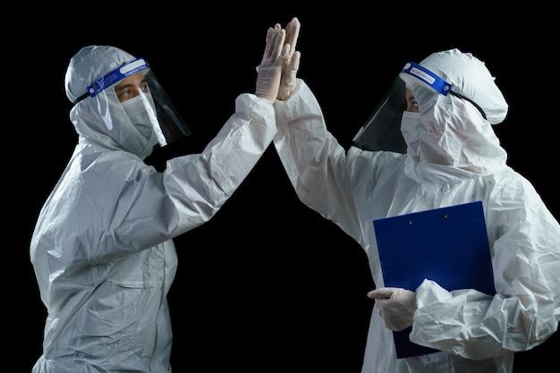 Lekarz noszący śoi i osłonę twarzy, którą świętują, by powstrzymać wybuch covid-19, udany.