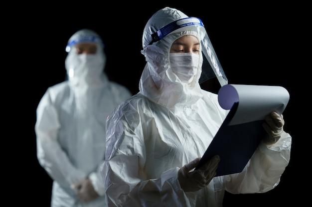 Lekarz noszący środki ochrony indywidualnej i osłonę twarzy szukający raportu z badań laboratoryjnych wirusa korony / covid-19.