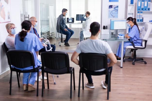 Lekarz noszący wizjer jako środek ostrożności podczas badania w sali szpitalnej i grupie osób w poczekalni