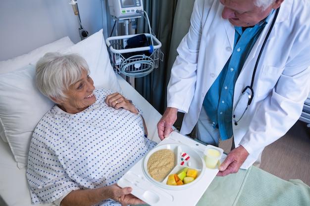 Lekarz obsługujący śniadanie i lekarstwa dla starszego pacjenta