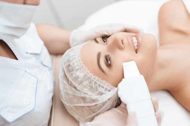Lekarz oczyszcza skórę kobiety specjalnym urządzeniem medycznym.