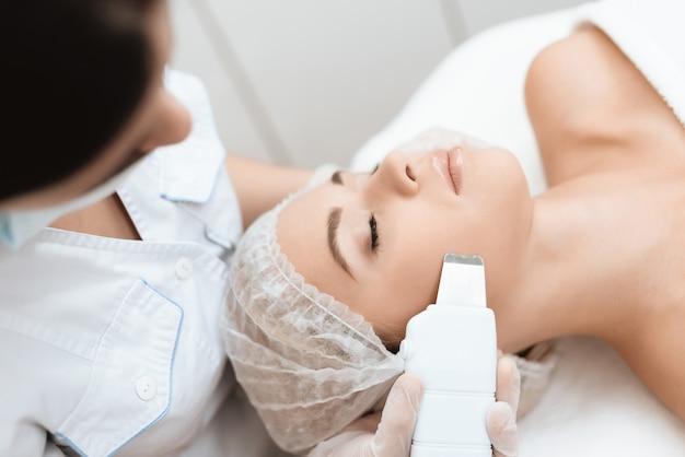 Lekarz oczyszcza skórę kobiety za pomocą specjalnego urządzenia medycznego.