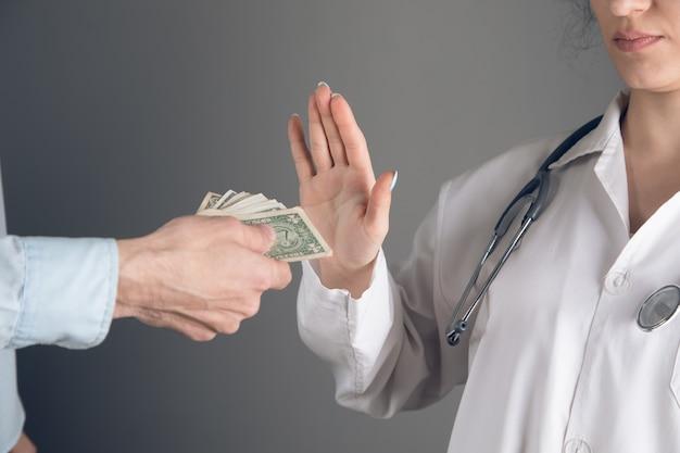 Lekarz odmawia przyjęcia pieniędzy na szarej ścianie