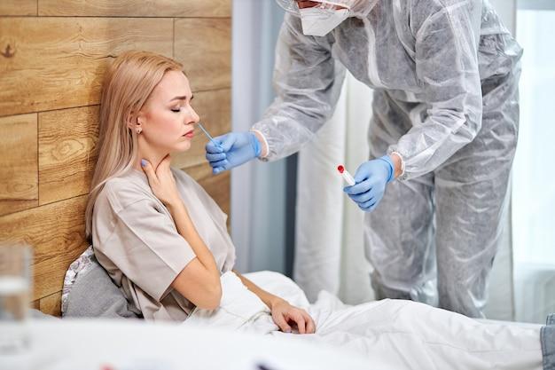 Lekarz odwiedzający niezdrową chorą kobietę w domu, wykonujący testy na koronawirusa covid-19. doświadczony lekarz w garniturze konsultuje pacjenta siedzącego na łóżku. cierpliwa opieka. diagnostyka. widok z boku