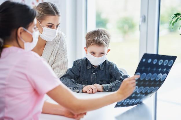 Lekarz omawia wyniki prześwietlenia z mamą i jej synem, którzy noszą maski z powodu covid-19