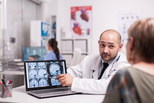 Lekarz omawia z senior kobietą z alzheimerem w biurze szpitala, wskazując na ekran laptopa z tomografem komputerowym. medyk ubrany w biały fartuch. pielęgniarka w niebieskim mundurze pracuje na komputerze.