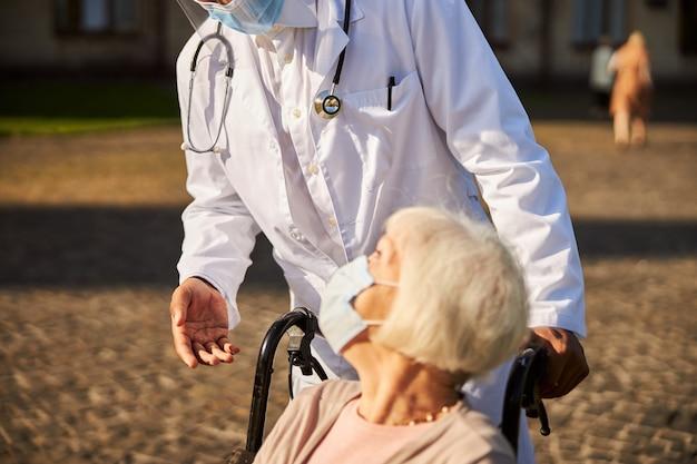 Lekarz oparty o staruszkę w masce siedzącą na wózku inwalidzkim