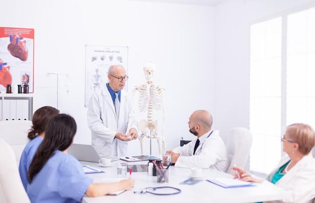 Lekarz opieki zdrowotnej posiadający prezentację o użyciu anatomii człowieka. ekspert kliniczny terapeuta rozmawiający z kolegami o chorobie, specjalista od medycyny