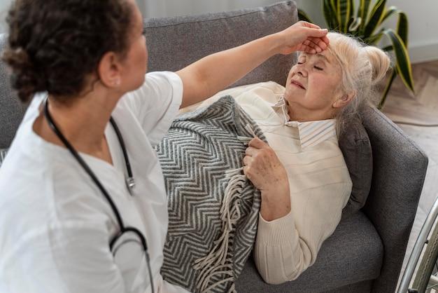 Lekarz opiekuje się starszą kobietą w domu
