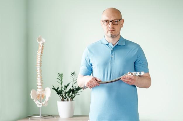 Lekarz osteopata-mężczyzna trzymający nierdzewne narzędzie do leczenia iastm używane do leczenia tkanek miękkich, mobilizacji tkanek miękkich wspomaganej przez snstrument i ostatecznego uwolnienia powięzi