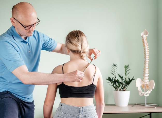 Lekarz osteopata wykonujący manipulacje uwalnianiem powięzi za pomocą leczenia iastm, dziewczyna otrzymująca leczenie tkanek miękkich na szyi za pomocą narzędzia ze stali nierdzewnej