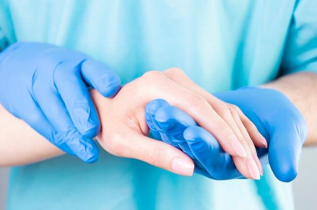 Lekarz ostrożnie trzyma pacjenta za rękę