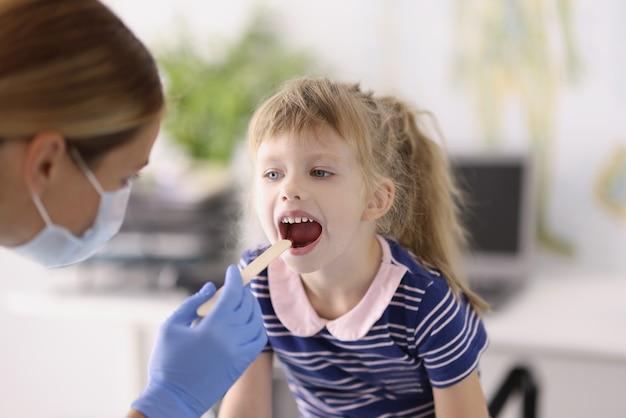 Lekarz otorynolaryngolog w ochronnej masce medycznej badający gardło małej dziewczynki drewnianą łopatką