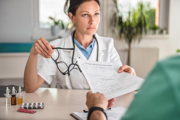 Lekarz otrzymujący formularz rejestracyjny pacjenta